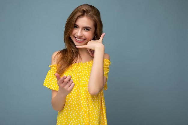 Schöne lächelnde glückliche junge blonde frau, die stilvolles gelbes sommerkleid trägt, das lokal steht