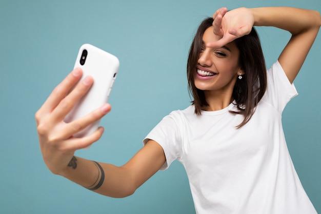 Schöne lächelnde glückliche junge brünette frau, die lässiges weißes t-shirt trägt, isoliert über blauem hintergrund der wand, das handy hält und benutzt, das selfie auf gadjet-bildschirm betrachtet.