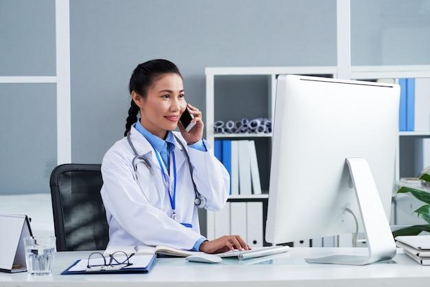 Schöne lächelnde hausärztin, die mit dem patienten telefoniert, wenn sie die ergebnisse von ...