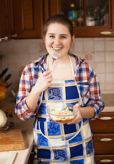 Schöne lächelnde hausfrau, die salat auf küche isst
