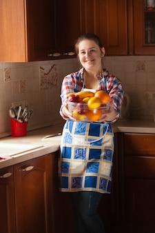 Schöne lächelnde hausfrau, die schüssel mit früchten hält