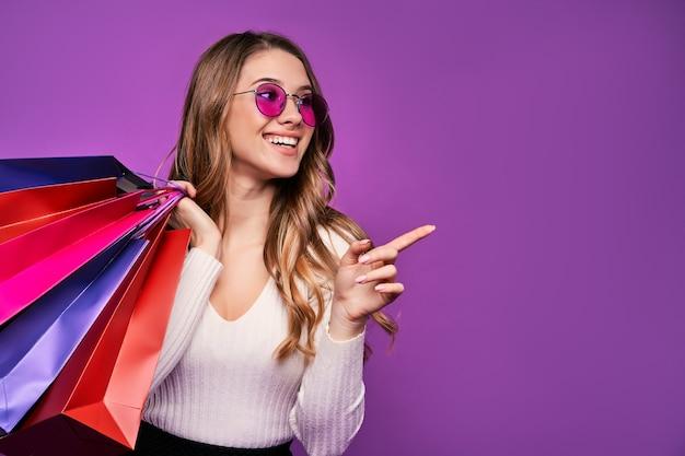 Schöne lächelnde junge blonde frau, die mit sonnenbrille zeigt, die einkaufstaschen und kreditkarte auf einer rosa wand hält