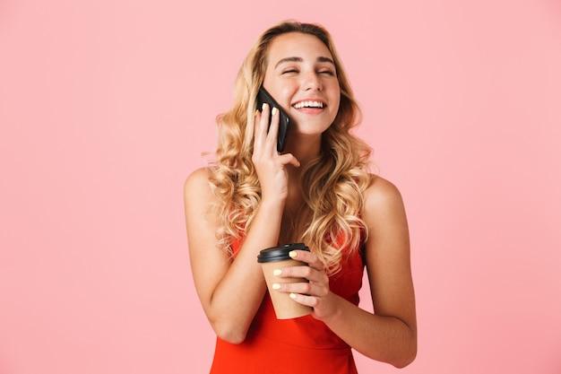 Schöne lächelnde junge blonde frau im sommerkleid steht isoliert über rosa wand, telefoniert mit dem handy, während sie eine tasse zum mitnehmen hält