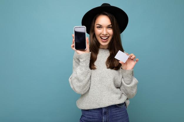 Schöne lächelnde junge brünette frau mit schwarzem hut und grauem pullover einzeln auf blauem hintergrund mit kreditkarte und handy mit leerem display für modell mit blick in die kamera.