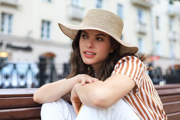 Schöne lächelnde junge brunettefrau, die auf bank im park sitzt.