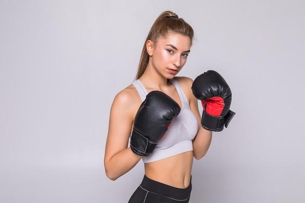 Schöne lächelnde junge fitnessfrau trägt boxhandschuhe
