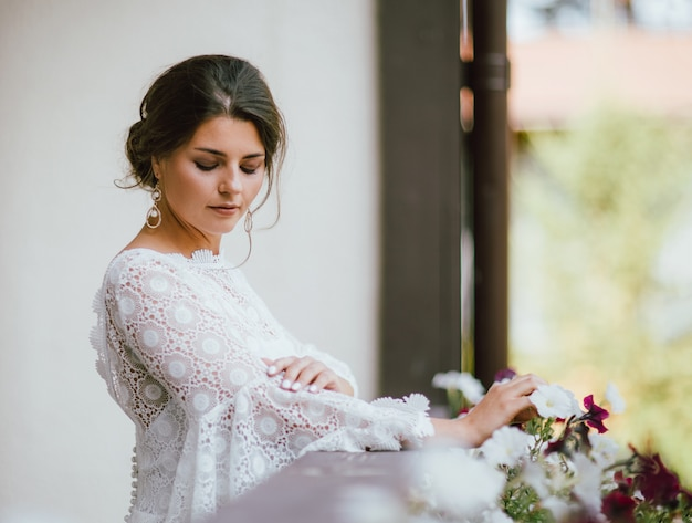 Schöne lächelnde junge frau des braut brunette im weißen spitzekleid auf balkon,