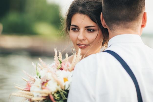 Schöne lächelnde junge frau des braut brunette mit boho artblumenstrauß mit bräutigam
