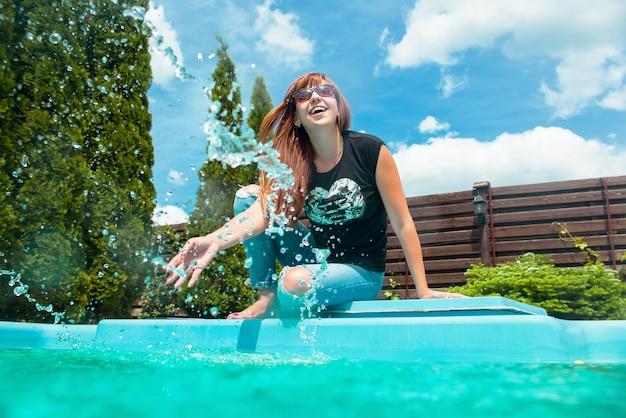 Schöne lächelnde junge frau des roten haares nahe swimmingpool im sommer