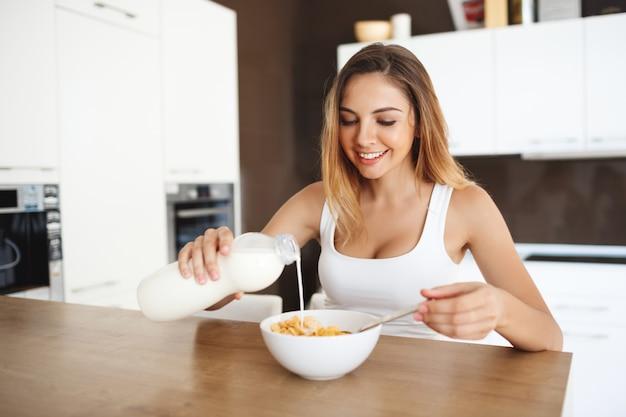 Schöne lächelnde junge frau, die am esstisch sitzt, der frühstück hat