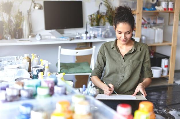 Schöne lächelnde junge frau, die an der kunstschule studiert, die an hausaufgabe arbeitet, an der modernen geräumigen werkstatt sitzt und zeichnungen mit bleistift macht