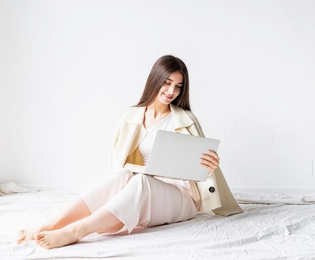 Schöne lächelnde junge frau, die auf dem boden sitzt und freiberufliches projekt auf laptop, unter verwendung computer tut