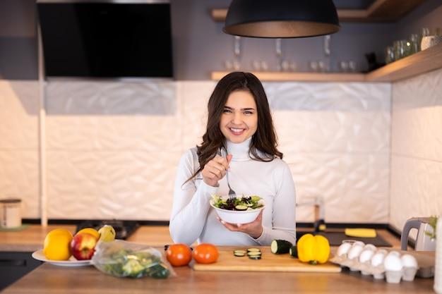 Schöne lächelnde junge frau, die gesundes essen mit viel obst und gemüse zu hause küche zubereitet.