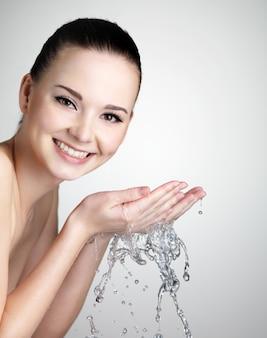 Schöne lächelnde junge frau, die ihr gesicht mit wasser - studioaufnahme wäscht
