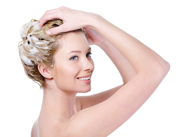 Schöne lächelnde junge frau, die ihr haar mit shampoo lokalisiert auf weiß wäscht