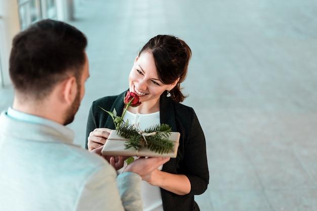 Schöne lächelnde junge frau, die rose und geschenk von ihrem freund empfängt.
