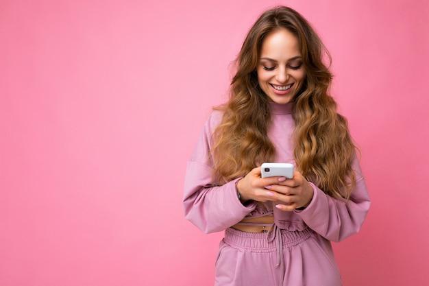Schöne lächelnde junge frau in freizeitkleidung, die isoliert über dem hintergrund steht und per telefon im internet surft und auf den mobilen bildschirm schaut.