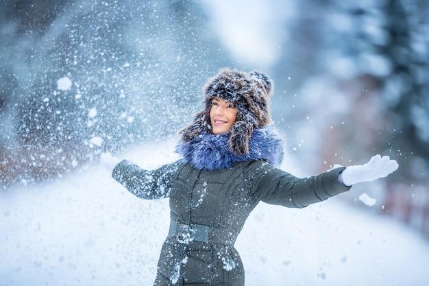 Schöne lächelnde junge frau in warmer kleidung das konzept des porträts bei verschneitem winterwetter