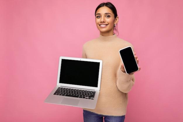Schöne lächelnde junge frau mit dunklem haar, das kamera betrachtet, die computer-laptop und handy hält