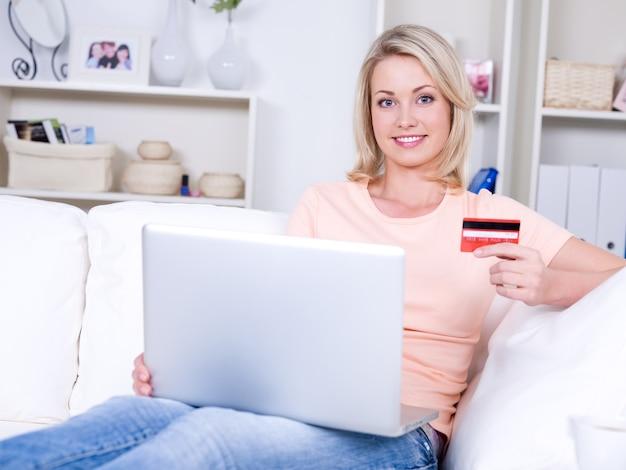 Schöne lächelnde junge frau mit laptop, die kreditkarte hält