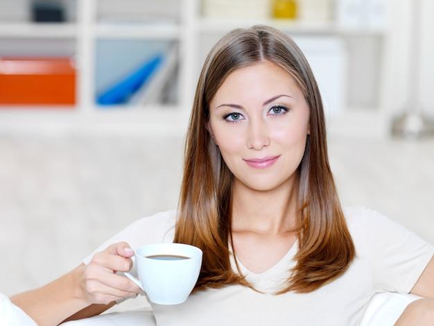 Schöne lächelnde junge frau mit tasse kaffee auf dem sofa - drinnen