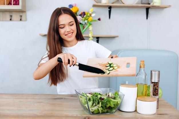 Schöne, lächelnde, junge frau schneidet gurke in salat, gesunde ernährung