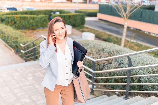 Schöne lächelnde junge geschäftsfrau mittleren alters, die auf dem smartphone auf der straße spricht, die treppe hinaufgeht, erfolgreiches arbeitsfrauenkonzept, kopienraum