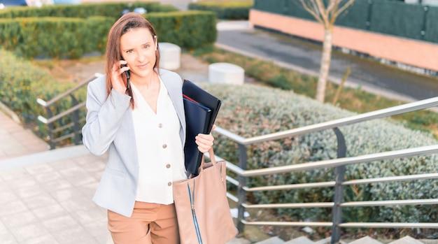 Schöne lächelnde junge geschäftsfrau mittleren alters, die auf dem smartphone auf der straße spricht, die treppe hinaufgeht. erfolgreiches arbeitsfrauenkonzept. platz kopieren