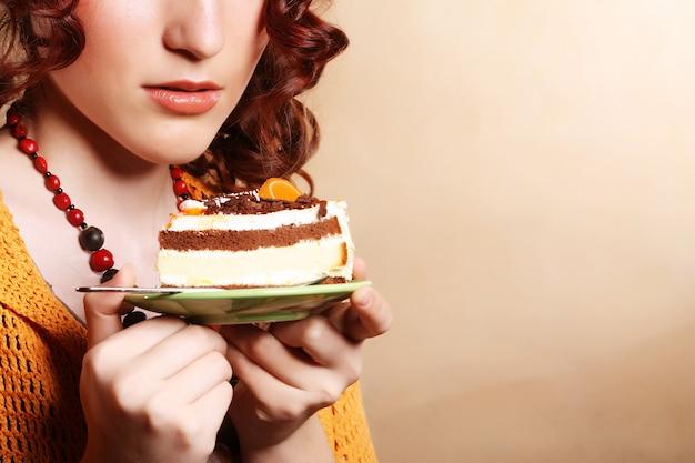 Schöne lächelnde junge lockige frau mit einem kuchen