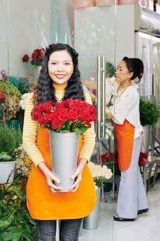 Schöne lächelnde junge vietnamesische frau, die im blumenladen mit eimer der roten rosen steht
