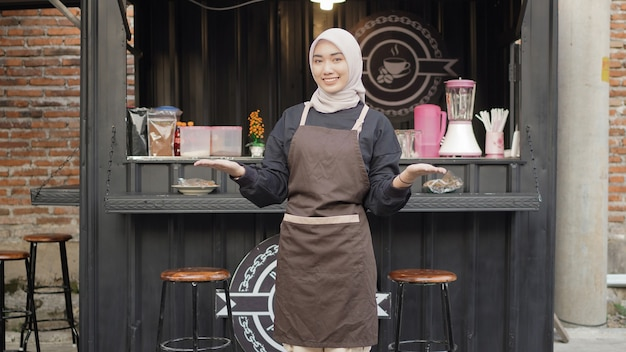 Schöne lächelnde kellnerin, die bereit ist, kunden am café-standcontainer zu begrüßen?