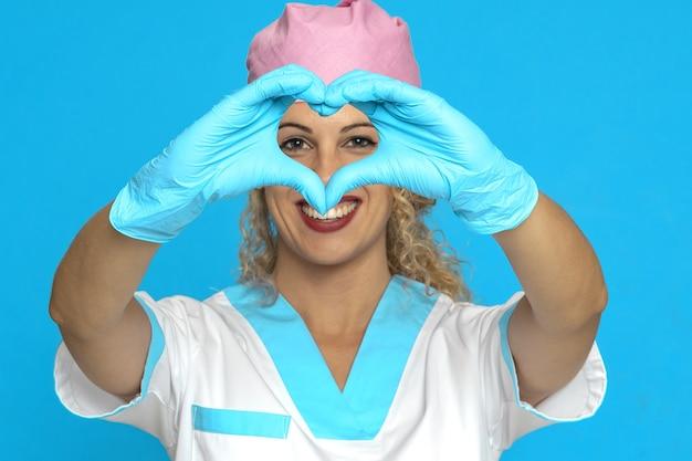 Schöne lächelnde krankenschwester, die ein herz mit den händen zeigt