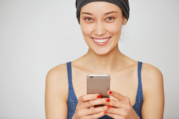 Schöne lächelnde lässige frau, die smartphone hält