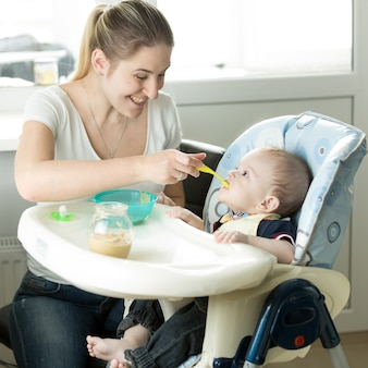 Schöne lächelnde mutter, die ihr baby auf küche füttert