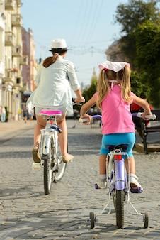 Schöne lächelnde mutter und tochter, die ein fahrrad reitet.