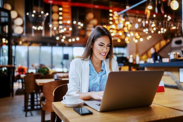 Schöne lächelnde positive modische kaukasische anwältin, die im café sitzt