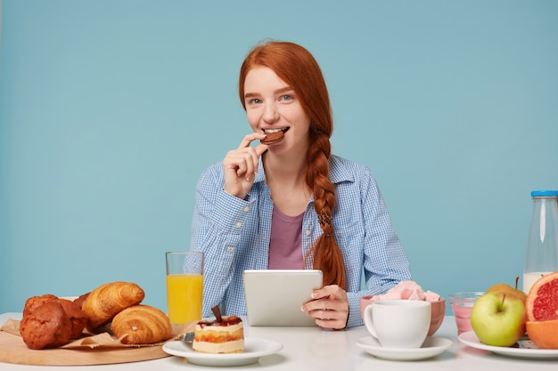 Schöne lächelnde rothaarige frau, die frühstück liest, das nachrichten in ihrem tablett liest, das vorne schaut und schokoladenkeks isst