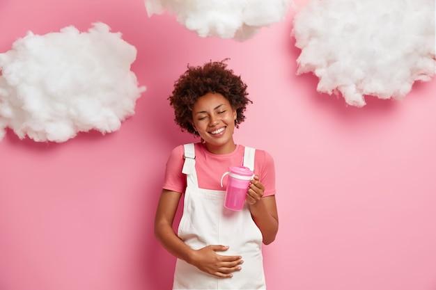 Schöne lächelnde schwangere lockige frau berührt bauch mit der hand, drückt liebe zum ungeborenen baby aus, trinkt wasser, erwartet, glückliche mutter zu werden, entspannt sich draußen. mutterschafts- und schwangerschaftskonzept