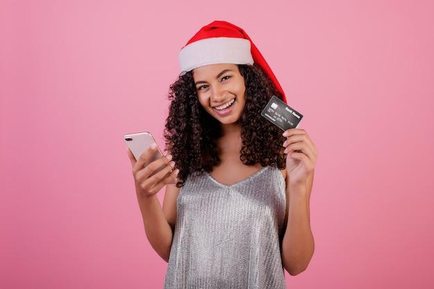 Schöne lächelnde schwarze frau mit dem telefon und kreditkarte, die sankt-hut tragen