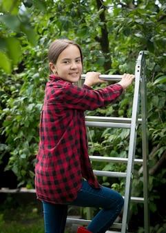 Schöne lächelnde teenager-mädchen im rot karierten hemd klettert die trittleiter im garten hoch