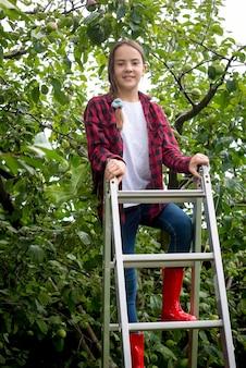 Schöne lächelnde teenager-mädchen klettert auf trittleiter im garten im hinterhof