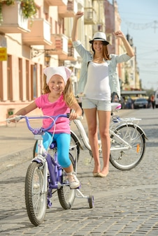 Schöne lächelnde tochter mit dem fahrrad die straße hinunter.