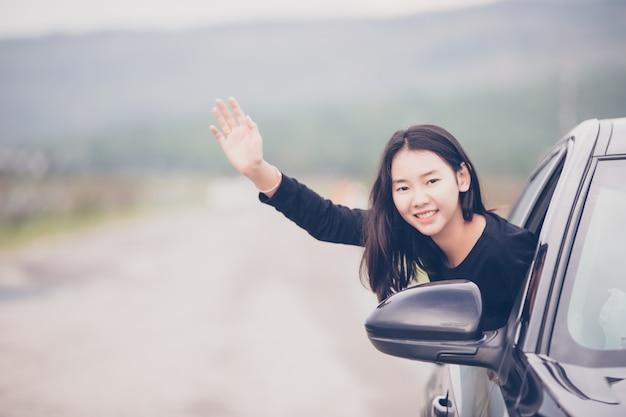 Schöne lächelnde und genießende asiatin fahren eines autos auf straße für reise