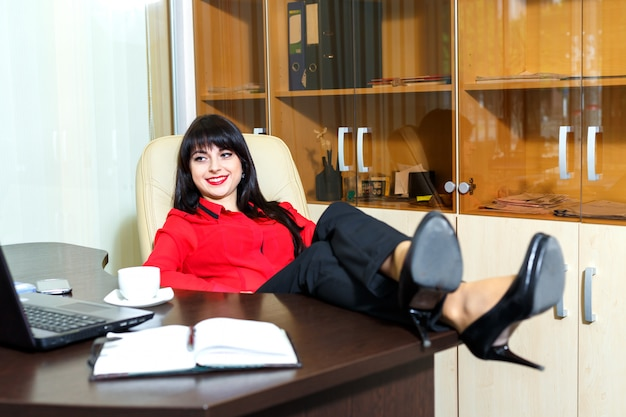 Schöne lächelnfrau entspannen sich in einem büro