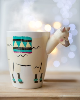 Schöne lamaförmige trendige tasse mit heißem tee mit lichtern