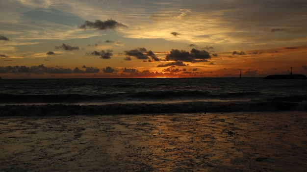 Schöne landschaft am strand mit sonnenuntergang und wolken in bali, indonesien