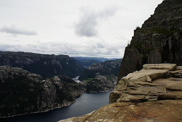 Schöne landschaft der berühmten preikestolen klippen nahe einem see unter einem bewölkten himmel in stavanger, norwegen