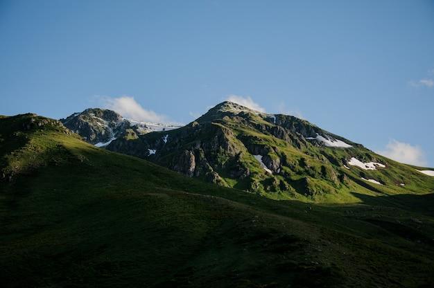 Schöne landschaft der felsigen hügel mit gras mit den schneeresten