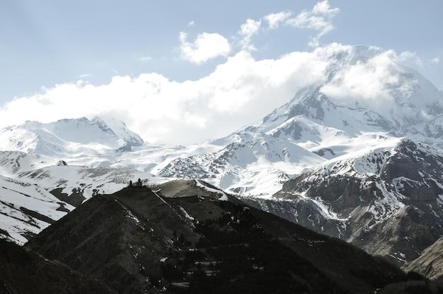 Schöne landschaft der felsigen und schneebedeckten berge auf dem land