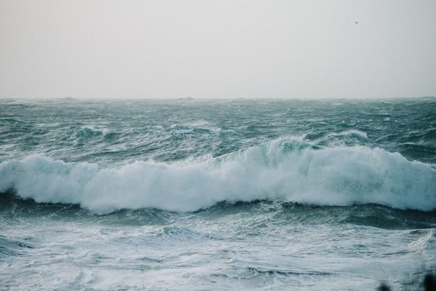 Schöne landschaft der meereswellen, die über felsformationen krachen